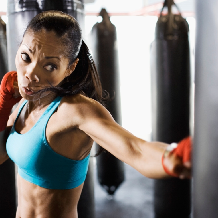 Woman hitting punching bag